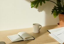 a coffee cup and a journal on a desk